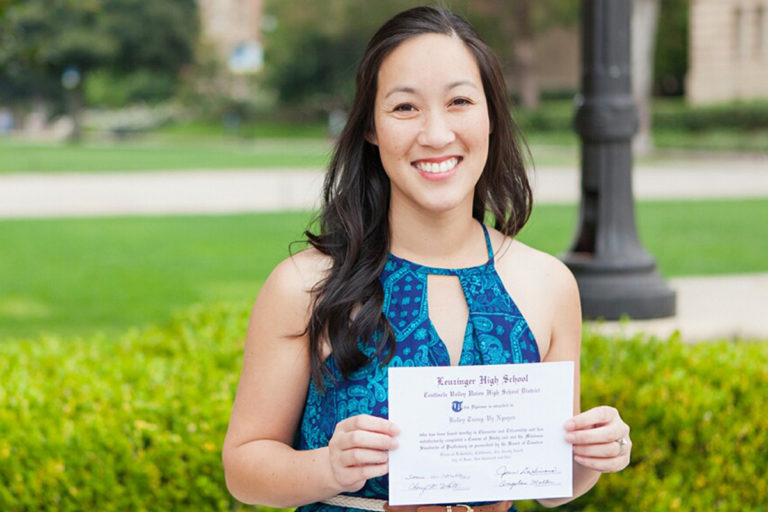 Dr. Le holding her high school diploma at UCLA.